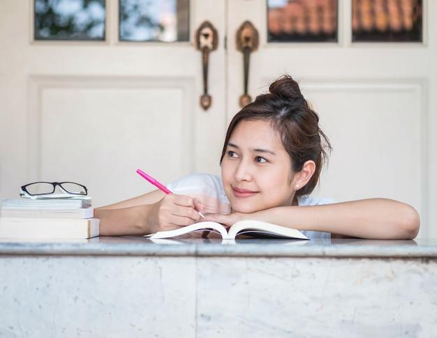 家の前に大理石のテーブルの上の本との幸せそうな顔を持つ女性