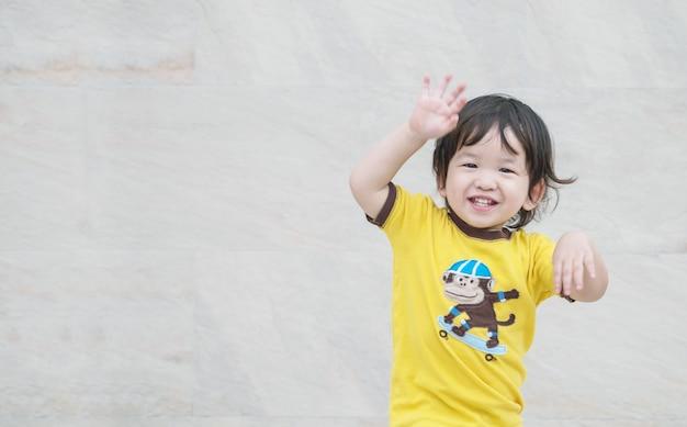 クローズアップは大理石の石の壁のテクスチャ背景の笑顔でアジアの子供を楽しむ