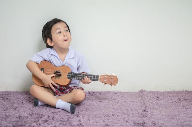 Крупным планом маленький ребенок в студенческой форме играть укулеле на ковер с копией пространства