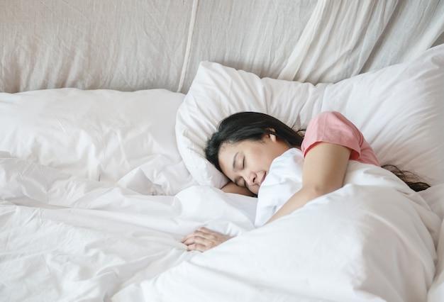 クローズアップアジアの女性は朝の寝室の背景で毛布の下のベッドで寝る
