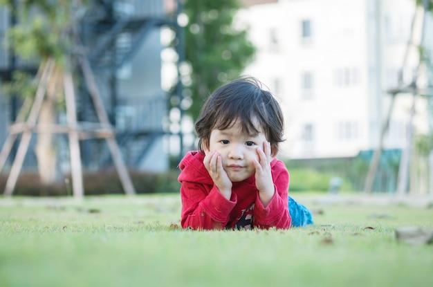 クローズアップアジア子供かわいい動きと庭の背景の芝生の床に嘘をついた