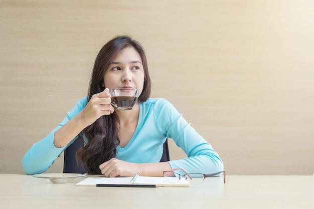 Женщина сидит за чашечкой кофе с мыслями на деревянном столе в конференц-зале