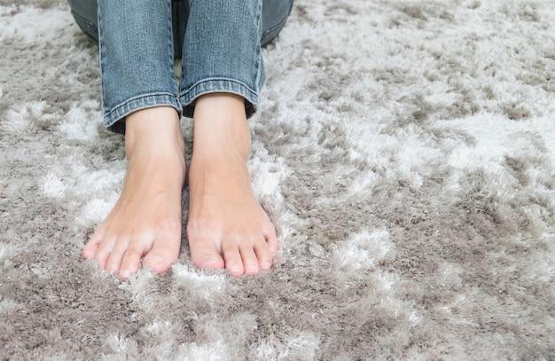 灰色のカーペットの床の上に座ってアジアの女性の足をクローズアップテクスチャ背景の家