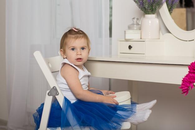 Милая девочка смотрит на свое отражение в белой спальне с круглым зеркалом