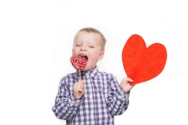バレンタインデーのコンセプト-赤いハートを持つ少年。スタジオの白い背景に分離