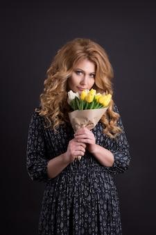 花の花束と黒の孤立した背景のスタジオでポーズ美しい白人少女