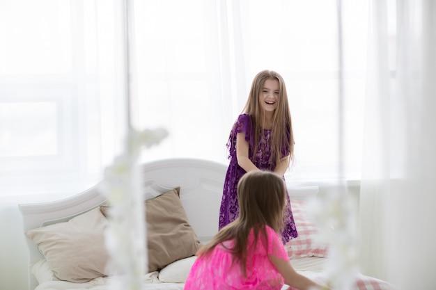 ピンクと紫のプリンセスドレスでかわいい女の子が白いベッドで笑う