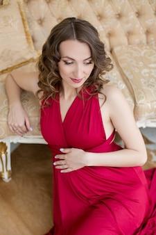 赤いドレスで妊娠中の女の子