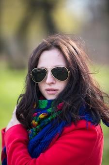 Красивая молодая леди в красном пальто и черных очках