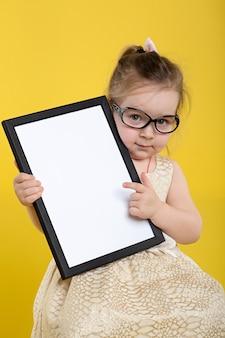 美しいドレスと黄色の背景にメガネのボードを持つ少女