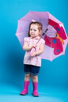 Очаровательная маленькая девочка с розовым зонтиком на синем фоне
