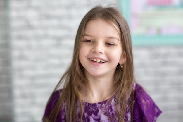Милая маленькая темноволосая девушка в фиолетовом платье в студии