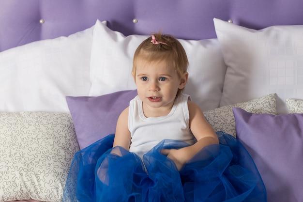 青いプリンセススカートで美しい少女がベッドに座っています。