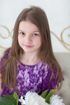 Довольно темные волосы девушка в фиолетовом платье принцессы на белом диване с пионами