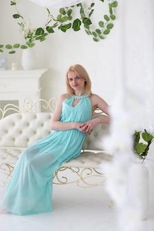 ネイビーギリシャドレスで美しい金髪の女性