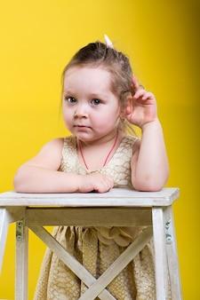黄色の背景に椅子と美しいドレスの少女