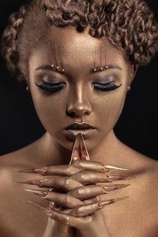 黄金の化粧と長い爪を持つ美しい白人少女