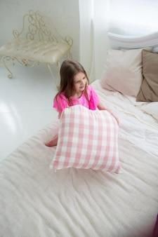 キュシンと白いベッドでピンクと紫のプリンセスドレスのかわいい女の子