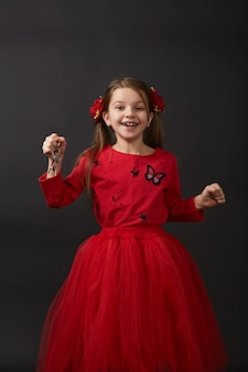 Красивая кавказская девушка держа ключи от машины, квартиру. ребенок в красной одежде очень счастлив