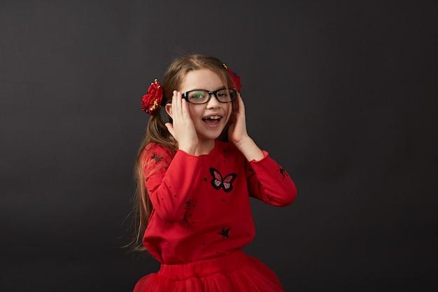 Очень милая девушка смотрит в очки, слегка держа их за руку