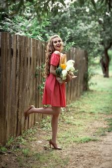 Красивая кавказская девушка в красном платье, держа сумку с едой