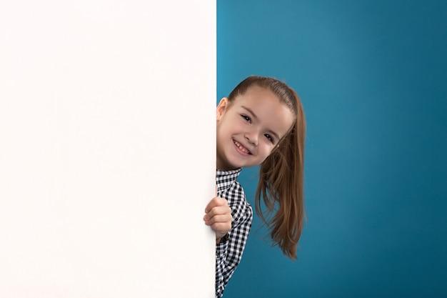 美しい白人ブルネットの子供は空のポスターを保持します。