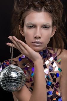 Красивая молодая кавказская женщина держа шарик диско