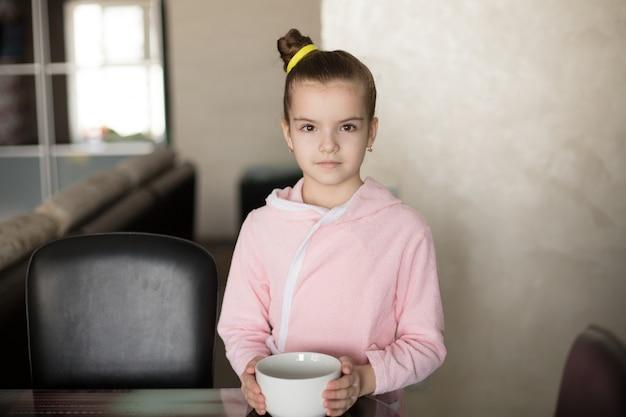 ローブの中の小さな女の子が手に皿を持っていて、朝食を食べようとしています。
