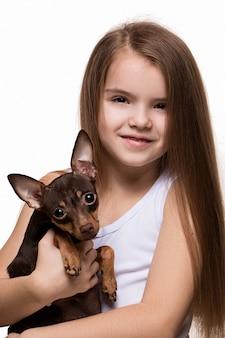 Портрет красивой молодой девушки кавказской прижимаясь с милый щенок терьера
