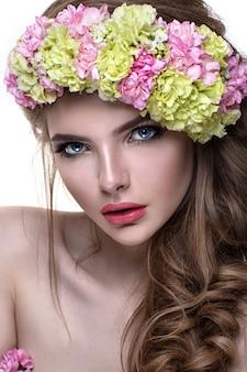 花の冠を持つ若い女。彼女の頭の上の花を持つ美しい女の子。