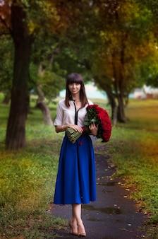 大きな花束を持つ美しい少女。笑顔とバラを保持している女性