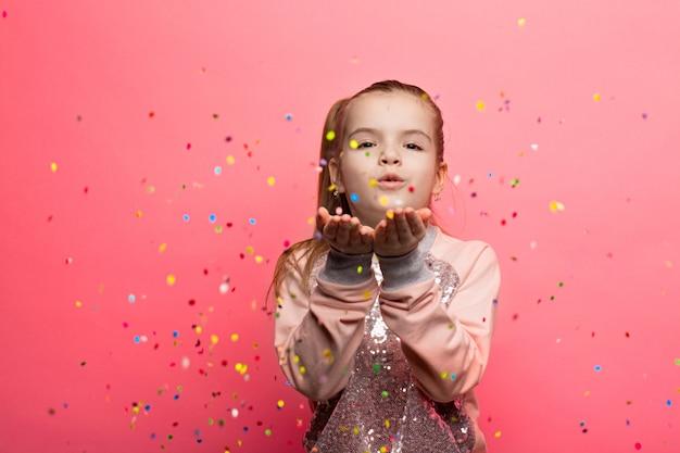 ピンクの背景を祝う幸せな女の子