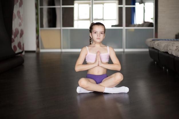 ヨガのポーズでマットの上に座っていると瞑想の白人少女。