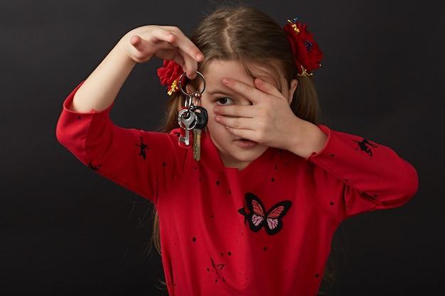彼女の目を閉じる女の子は車の鍵の束を送ります