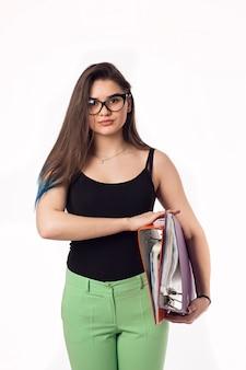 カラフルなフォルダーとメガネでかなりブルネットの学生少女