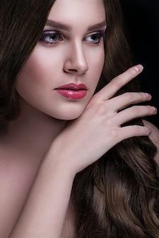 長い髪と化粧のポーズを持つ美しいブルネット