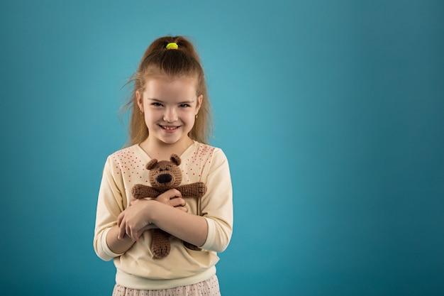 彼女の手にテディベアを持つ少女の肖像画