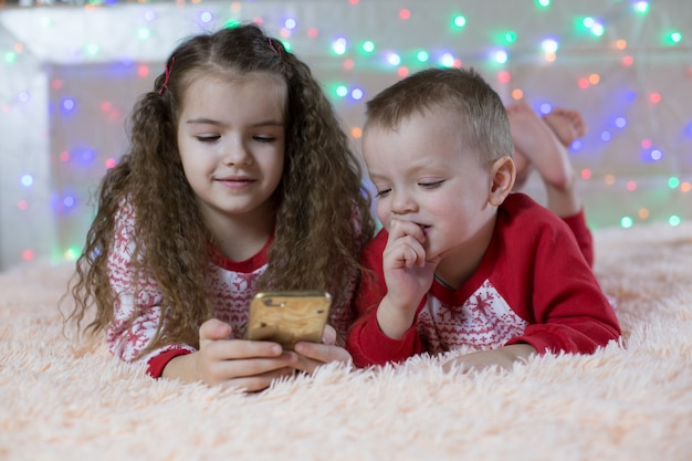 スマートフォンで遊ぶクリスマスパジャマの子供たち