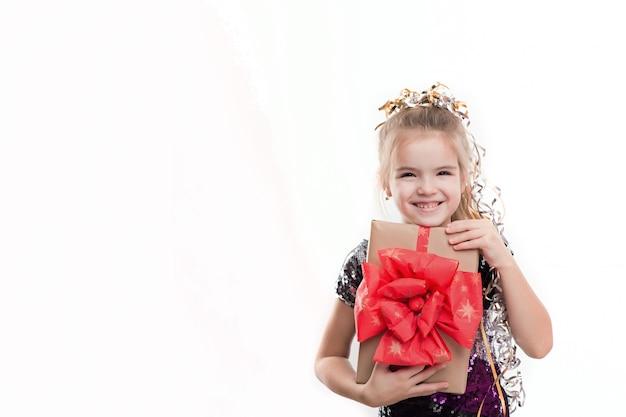 白い壁にギフトボックスを持つ美しい少女の写真