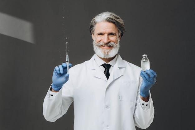 手袋と医療マスクの古い男性医師が注射器を保持しています。