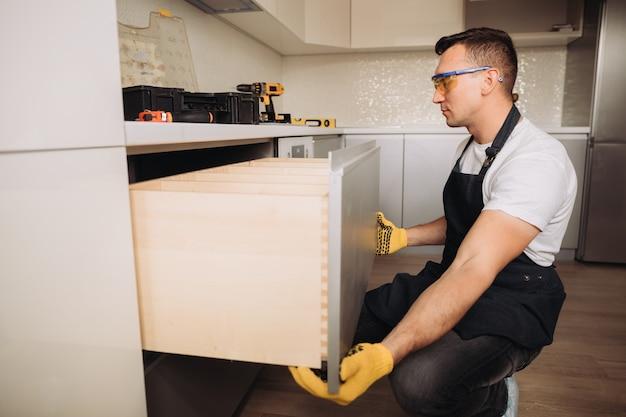 Человек обслуживания устанавливая кухонную мебель