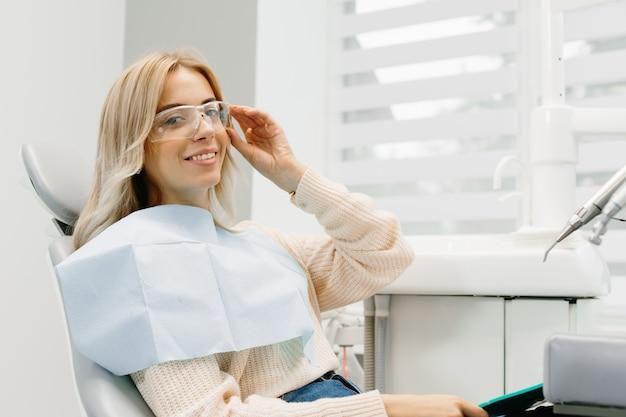 彼女の歯を見ている女性。歯科医院で笑顔の女性。