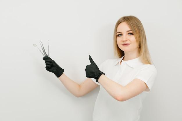 Блондинка доктор дает большие пальцы в офисе стоматолога