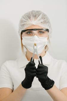 Стоматолог держит удаленный зуб в стоматологической клинике с черными перчатками
