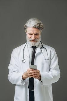 灰色の壁にドクターセンサーの肖像画。電話で話している白衣を着た白髪の主任医師。