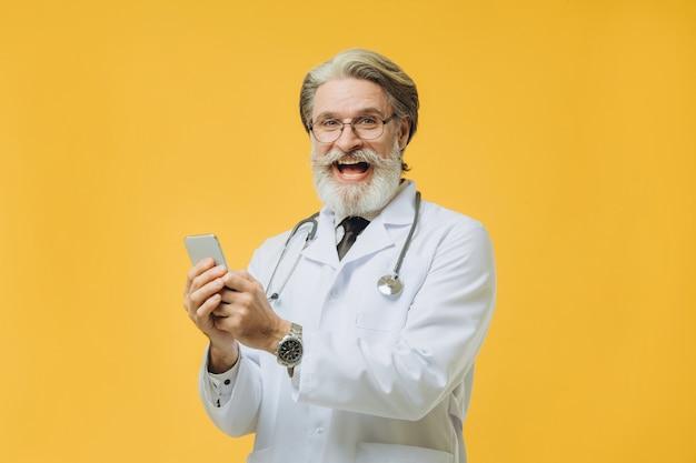 電話で話している白衣を着た白髪の先輩医師。