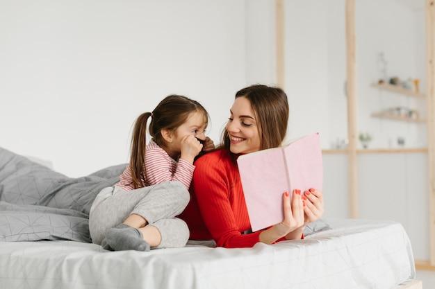 ベッドで横になっている本を読んで幸せな家族の母と子の娘