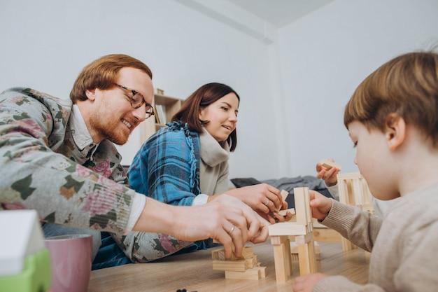 若いお母さんとお父さんが子供たちと教育ゲームをする