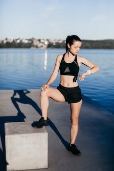 Спортивная девушка, одетая в черное, прогревается перед бегом, утром на детской площадке на городском пляже
