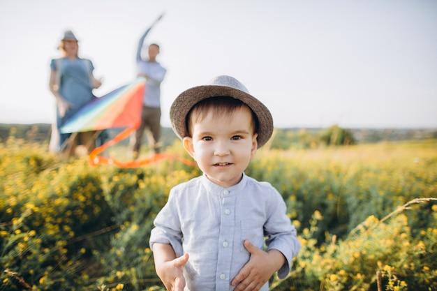 Счастливая семья, отец матери и ребенка, сын запускают воздушный змей на закате